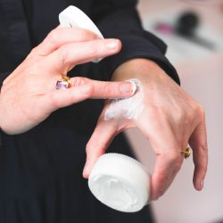 A woman applying a hydrating skin care product from the Veil range to her skin to fight the signs of ageing