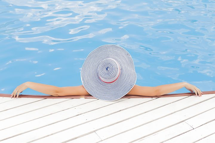 This is an image of an individual in a pool wearing a large hat.