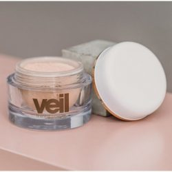 This is an image of Veil Finishing Powder, a finely milled setting powder to help increase the wear time and longevity of Veil Cover Cream and other concealers and foundations. The product is available in two shades, Translucent for light skin tones and Dusk, a shade for warmer and deeper skin tones.