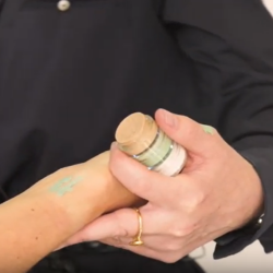 This is an image of a tattoo being concealed with a a green colour correcting concealer.