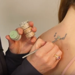 This is an image of a tattoo being concealed using high coverage makeup Veil Cover Cream to hide its appearance.